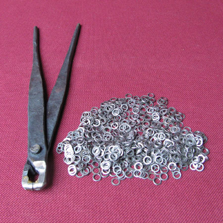 Spare chainmail links, alternately riveted, plus riveting tool